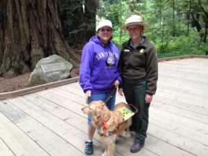 Ranger Lucy in uniform standing with me and my guide dog