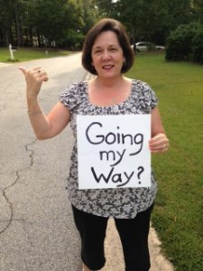 "Audrey on the side of the road with her thumb out and a sign that reads ""Going My Way?"""